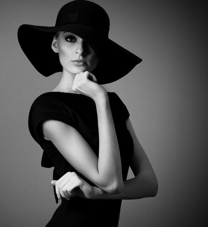 Woman wearing black hat and black dress