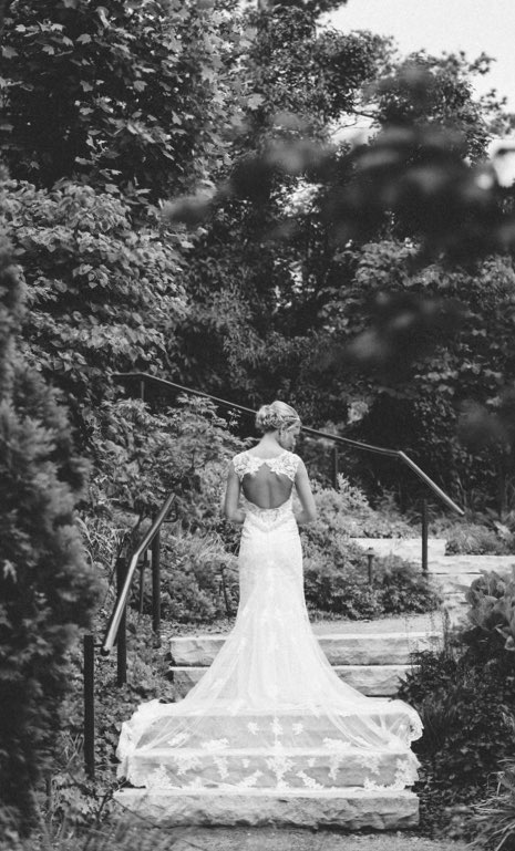 A bride on her wedding day, standing outside, in front of a staircase, with her back to the camera