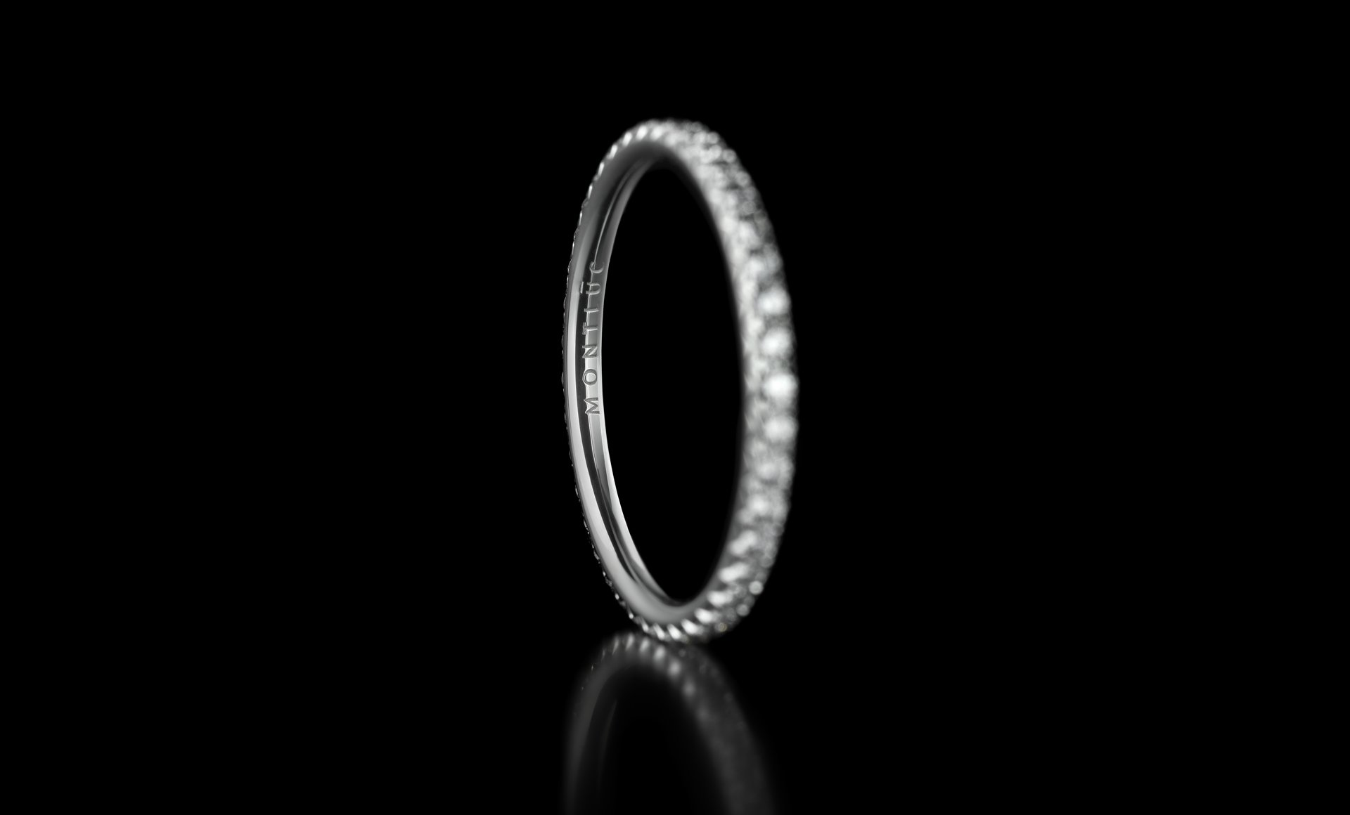 Montluc - Halo No 1 diamond ring, viewed from an angle, with engravement in focus.