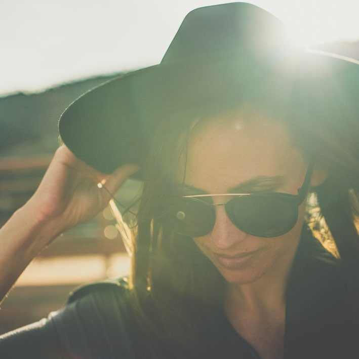 Woman with hat and sunglasses and her back to the light